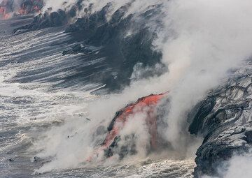 The lava flow advances a finger of new land over the young shore. (Photo: Tom Pfeiffer)