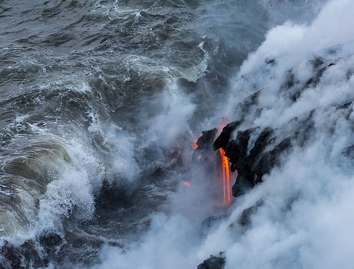 Wave breaking in front of a beautiful lava hose streaming down into the water. (Photo: Tom Pfeiffer)