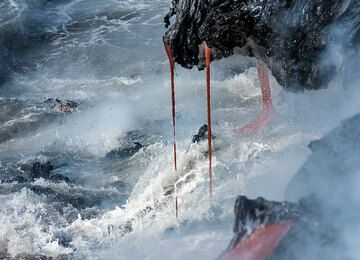 Lava drips into the agitated ocean water. (Photo: Tom Pfeiffer)