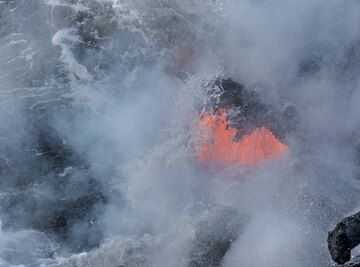 The lava continues to push forth even when submerged by the wave. (Photo: Tom Pfeiffer)