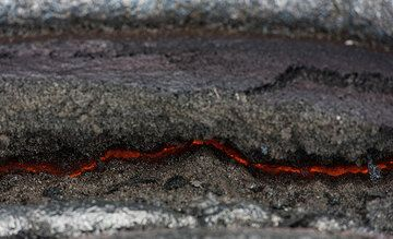 A crack reveals the still hot, glowing interior of the lava flow. (Photo: Tom Pfeiffer)
