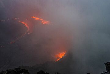 Heavy rain and fog prevent clear views of the degassing fountains along the margins of the lava lake. (Photo: Tom Pfeiffer)