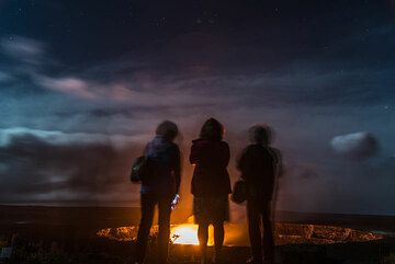 A group of friends stand on the terrace watching the lava lake in front of them. (Photo: Tom Pfeiffer)