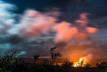 Small bushes and ohia trees stand out against the bright glow from thhe lava lake. (Photo: Tom Pfeiffer)