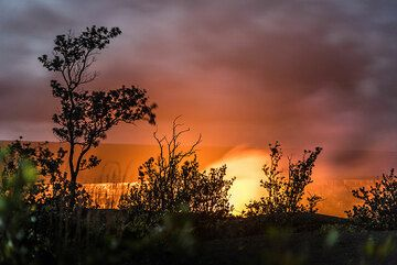 Zoom towards the lava lake behind silhouetted bushes. (Photo: Tom Pfeiffer)