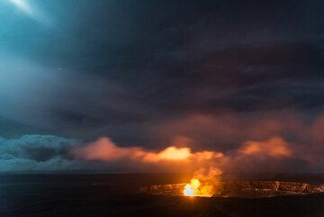 Denser and lower clouds drift over the lava lake and are pained red and yellow. (Photo: Tom Pfeiffer)