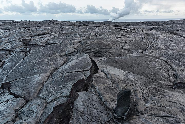 The vast lava field of the g61 flow in the coastal flat - the steam plume from the active ocean entry in the background. (Photo: Tom Pfeiffer)