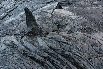 Something like this had happened here, leaving a triangle of old lava crust standing vertical like a frozen shark fin. (Photo: Tom Pfeiffer)