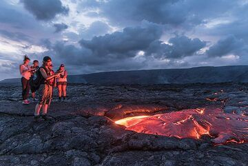 Group of young people at the lava flow illuminated by the red glow. (Photo: Tom Pfeiffer)