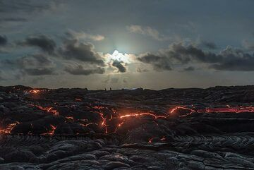 The blue hour is over, but still nearly full moon has risen. Flashlights and silhouettes of people are seen scattered around on the vast lava flow field. (Photo: Tom Pfeiffer)