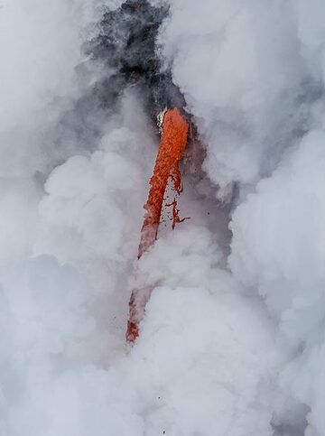 """A short-lived """"window"""" in the steam clouds lets the lava tube's mouth to be seen briefly. (Photo: Tom Pfeiffer)"""
