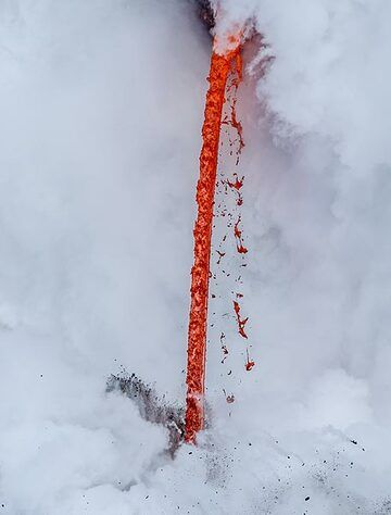 Liquid lava strands detach from the hose as it is falling and are twisted and torn into Pele's hair and curly shapes. (Photo: Tom Pfeiffer)