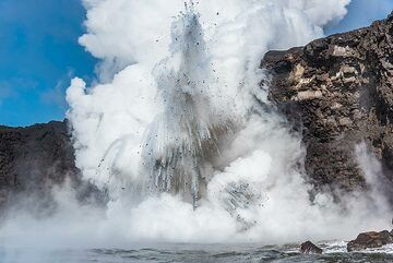 A larger explosion throws fragments well above the sea cliff. (Photo: Tom Pfeiffer)