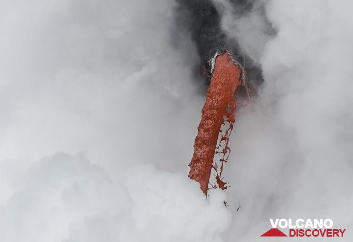 Zoom onto the mouth of the lava tube where the fire hose exits; today, it is not particularly strong, but still impressive. (Photo: Tom Pfeiffer)