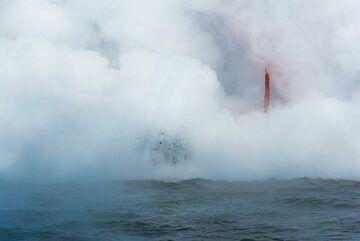 A glimpse of red lava inside the white steam. (Photo: Tom Pfeiffer)