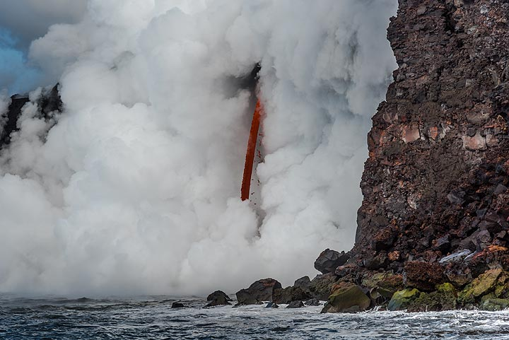 """From the exposed lava tube, a so-called """"fire hose"""" - a jet of lava - shoots out and pours into the sea. This lasted for almost 3 months (!), before a new delta started to form in late March. (Photo: Tom Pfeiffer)"""