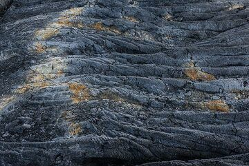 Old ropy pahoehoe lava with a crack encrusted with sulfur and other mineral deposits. This was once located above an active lava tube from which sulfur-rich gasses escaped, leaving these deposits. (Photo: Tom Pfeiffer)