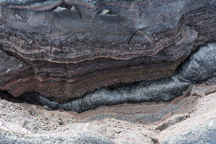 The lava field surface is full of plate-like structures like this one: a part of the surface of the flow had been lifted up by about 30 cm, caused by still active lava underneath while a small amount of lava oozed out from the base of the suture. This process is called inflation and contributes by far the largest volume to the growth of pahoehoe lava flows. (Photo: Tom Pfeiffer)