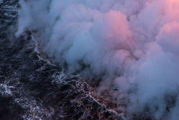 Bluish and pink steam from the lava entry hovering above the ocean surface. (Photo: Tom Pfeiffer)