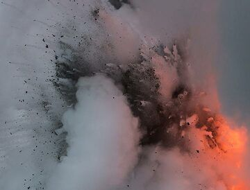 Dark, still dense masses of fragmented lava mixed with water and steam rise through the bluish steam chaos. (Photo: Tom Pfeiffer)