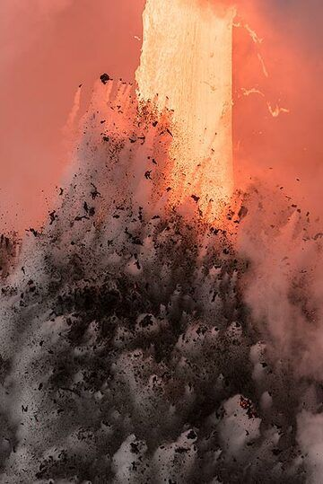 The powerful lava hose, about 2 meters wide, seen behind the explosion of water and rocks. (Photo: Tom Pfeiffer)