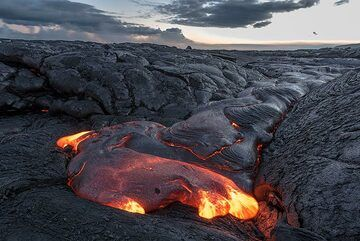 """On our last evening at the lava flows during the Kilauea Special tour, we find nice breakouts again about half way up between the coast and the base of the pali. An advancing lava flow is about to fill in a small """"valley"""". (Photo: Tom Pfeiffer)"""