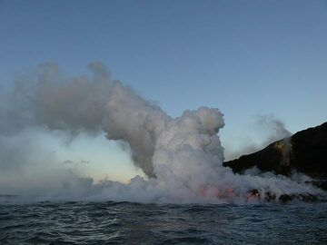 Day 5: Overview of the Kamukona ocean entry on 16 April 2017, with (right) below the yellow sulphur mineralisations the encased tube through which lava flows to eventually run down the lower cliffs into the sea (central right), creating a large steam plume (centeal) (Photo: Ingrid Smet)