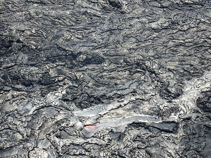 Extension day 3: Very fresh black to silvery pahoehoe lava flows with an actively flowing overland breakout (bottom centre) (Photo: Christina Metzger)