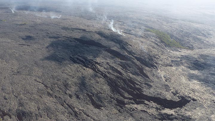 Extension day 3: Older lava flows that came down the pali left a kipuka (vegetation island) behind. More recent surface lava outbreaks are recognisable by their dark brown to black colour, the steam trail indicates where the lava is flowing underground in lava tubes to the ocean entry at Kamukona (Photo: Steven Van den Berge / Lana Van Heghe)