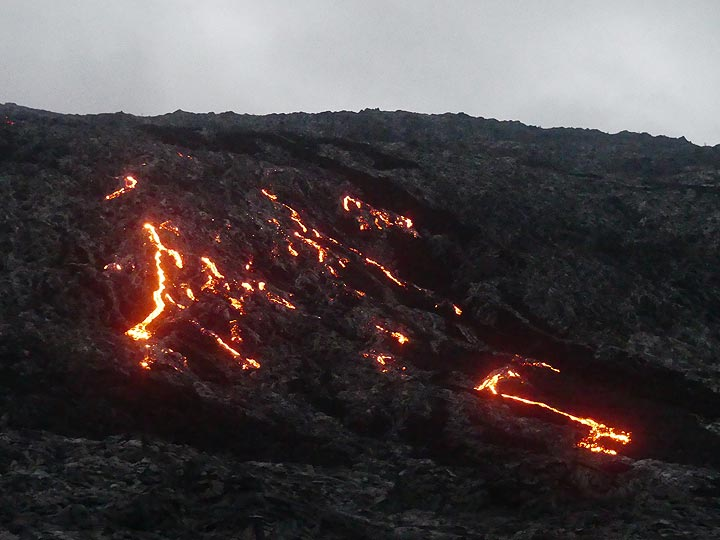 By dawn finally reach the bottom of the pali from where lava is flowing down - seemingly writing the initials of our tour guide Ingrid Smet? (Photo: Ingrid Smet)