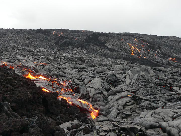 The active pahoehoe lava flow fronts that we found are advancing next to an older blocky aa lava flow (dark brown rocks in bottom left corner) (Photo: Ingrid Smet)