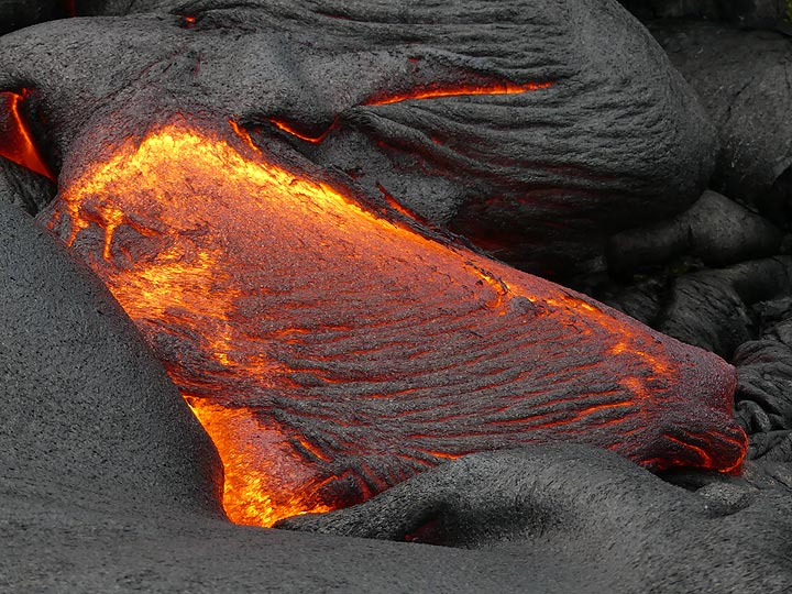 The outer surface of fresh red hot lava quickly forms a thing silvery crust, which is pushed forward by the underneath still flowing lava, and thereby crumpled into the typical ropey texture (Photo: Ingrid Smet)