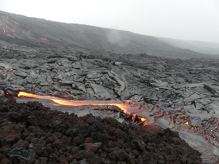 Actively flowing pahoehoe lava fronts at the bottom of (foreground) and halfway up (background left) the pali (Photo: Ingrid Smet)