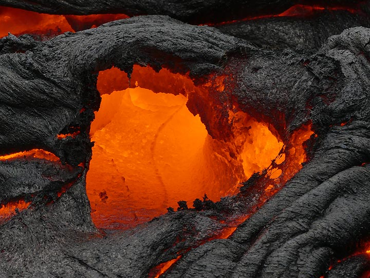 As the crust breaks open, a miniature skylight is formed, allowing us a look inside the red glowing hot interior of the active pahoehoe lava flow (Photo: Ingrid Smet)