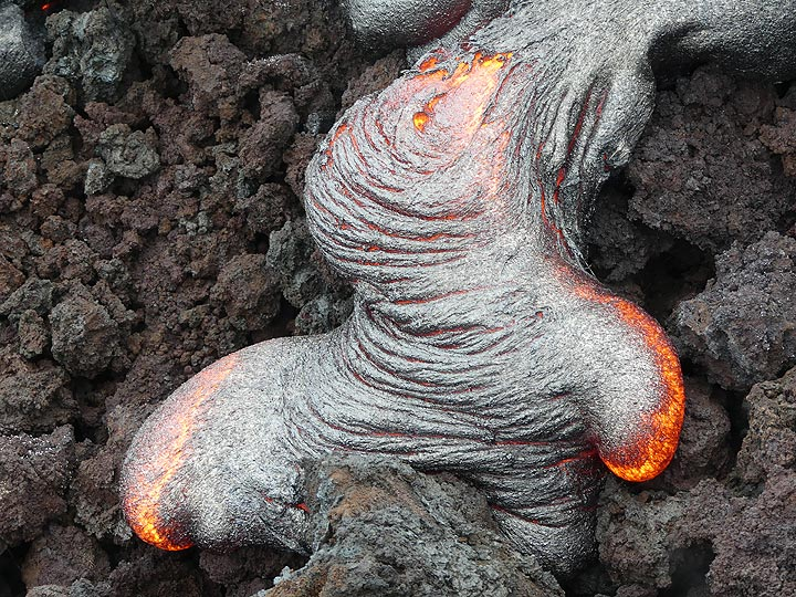 Fresh pahoehoe lava with silvery ropey textured crust slowly covers older aa lava (Photo: Ingrid Smet)