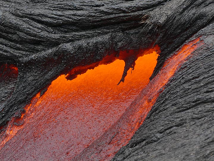 Close up of red hot liquid lava flowing from underneath a recently cooled crust (Photo: Ingrid Smet)
