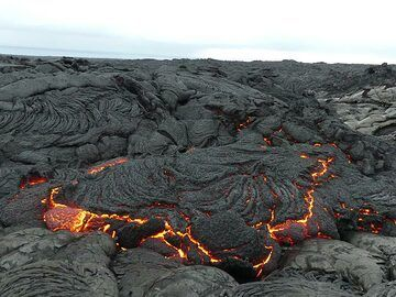 """In March 2018, lava continued to flow through the tube system of the so-called """"61g"""" lava flow episode of Kilauea volcano, which had started in late May 2016 and fed an active ocean entry during July 2016 - Nov 2017. Since then, the lava tube has been producing surface flows of varying size above and on the pali as well as near its base. The pictures presented here were taken by team member geologist Dr Ingrid Smet during a morning excursion on 16 Mar 2018. They show sluggish surface lava flows, as have been typical for the past weeks in this area near the base of Pulama pali. (Photo: Ingrid Smet)"""