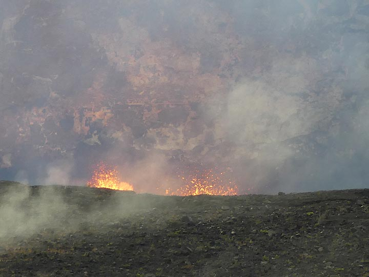 Large gas bubbles exploding through the lava lakes's surface continue to create lava spattering that is visible from the Jaggar Museum lookout (Photo: Ingrid Smet)