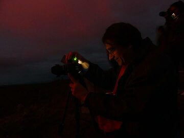 The red glow of the lava lake, 1 km away, reflects on the faces on early rise observers and photographers (Photo: Ingrid Smet)