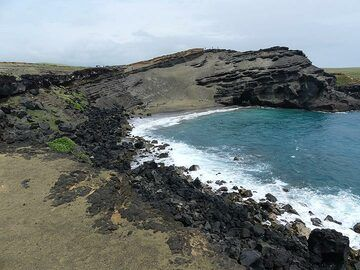 The layers of the scoria cone are build up of black lava droplets with green olivine crystals, the latter being heavier than the former and hence getting left behind and accumulated during wind and water action (Photo: Ingrid Smet)