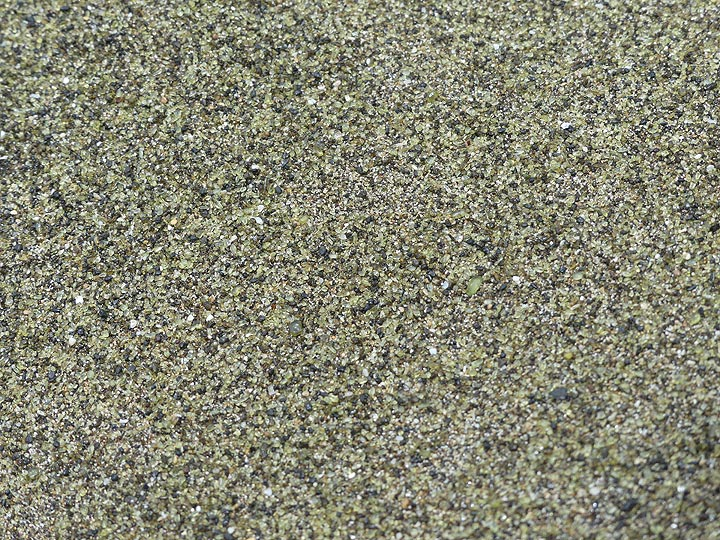 Close-up of the green sand at Green Sand Beach, made up mostly of green olivine crystals besides some black lava grains and white shell pieces (Photo: Ingrid Smet)