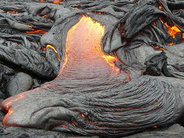 A larger outbreak pours pahoehoe lava onto the older lava fields, its thin crust quickly wrinkling together in the typical ropey texture (Photo: Ingrid Smet)