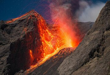 A stronger eruption sends many bombs against and over the vertical eastern crater wall. (Photo: Tom Pfeiffer)