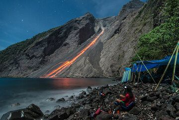 Glowing rockfalls after a nice night-time eruption; our camp to the right. (Photo: Tom Pfeiffer)