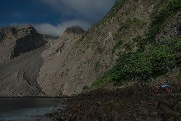 View of the cliff from our camp; our rubber boat in the lower right in the highest part of the beach. (Photo: Tom Pfeiffer)