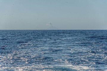 Batu Tara volcano seen in the far horizon, with an eruption plume. (Photo: Tom Pfeiffer)