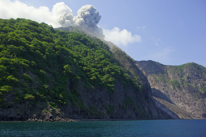 Sailing around its southern side, we get a first view of the prominent collapse scarp on the eastern side, similar to the Sciara del Fuoco of Italy's Stromboli volcano. An ash plume from an eruption greets us. (Photo: Tom Pfeiffer)