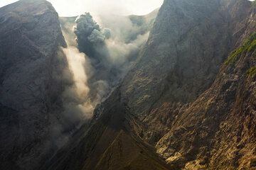 View into the upper half of the collapse scarp with the active crater in the center of the image. A typical strombolian eruption produces a small ash plume rising about 150 m in the image. (Photo: Tom Pfeiffer)