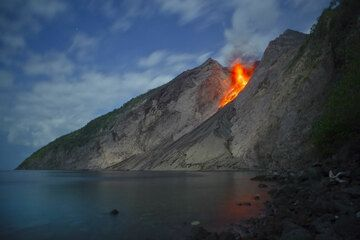 The photos were taken during 25-28 Nov 2012 when we visited the remote Komba island consisting of Batu Tara volcano during our recent volcano expedition to Indonesia. The volcano has been in continuous strombolian eruption, at fluctuating levels, since 2006. Very favorable weather and sea conditions allowed us to land several times on the narrow beach a few 100 m south of the eastern collapse scar of the volcano, the only place on shore from where the vent and its eruptions are visible. During our stay, activity varied from day to day, and consisted in frequent ash venting, mild to powerful strombolian eruptions accompanied by loud detonations and ejecting bombs to several hundred meters height above the vent, located at about 500 m elevation inside the deep collapse scar.   (Photo: Tom Pfeiffer)