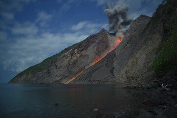 Strombolian explosion at night in moonlight with glowing lava blocks rolling down to the sea. (Photo: Tom Pfeiffer)